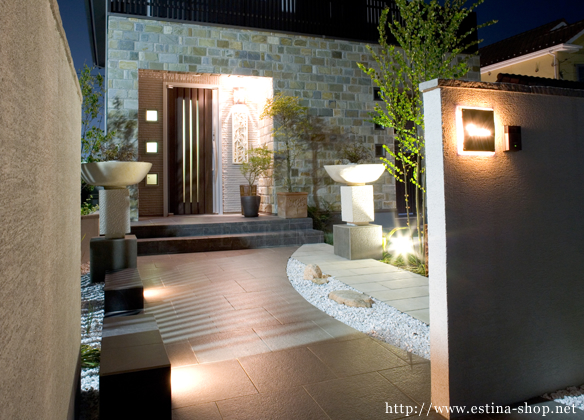 照明で浮かび上がる表札や、シンボルツリーを間接的に照らすアプローチ