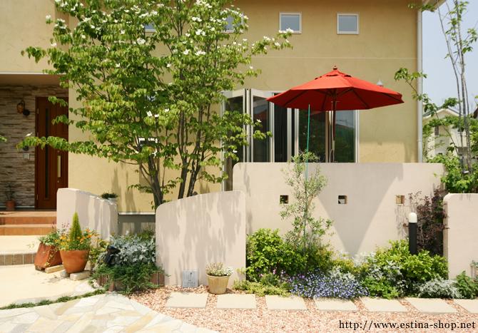 塗り壁と植物と赤いパラソルが印象的に