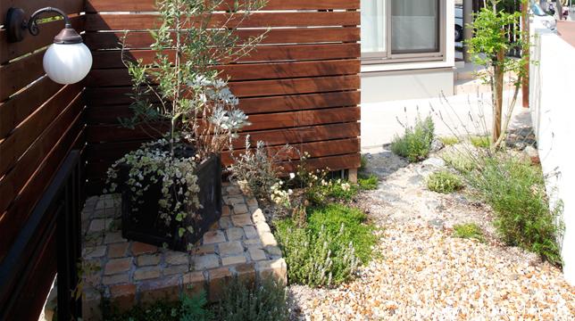 外からの目線も考慮したウッドフェンスと、アンティークレンガ造りの花台が印象的