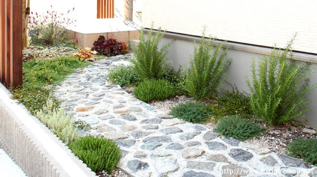 自然石を敷き詰めたナチュラルな小道はお庭へとつづく