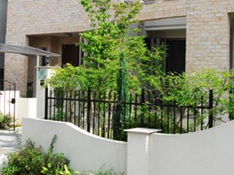 植物の緑とフェンスの黒が白い塗り壁をより印象的に