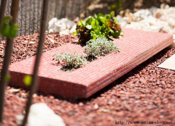 ハーブを植えた花壇が印象的な、赤で統一された空間