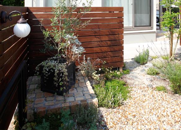 外からの目線も考慮したウッドフェンスとアンティークレンガ造りの花台が印象的
