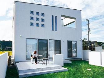 スタイリッシュな白い建物と美しく調和したテラス。ホワイトと芝生のグリーンのコントラストもきれい