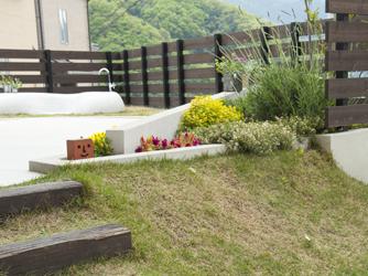 芝の傾斜にある花壇はより立体的に